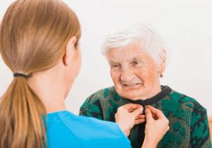 Caregiver helping elderly woman dress