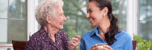 An elderly chatting happily with a caregiver