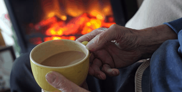 An elderly sitting next to a fireplace, drinking coffe