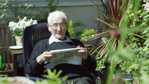 An elderly solving a crosswords puzzle in his armchair
