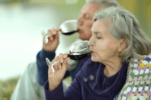 Elderly couple enjoying a glass of wine