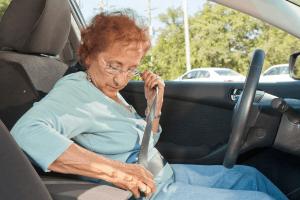 An elderly fastening the seatbelt