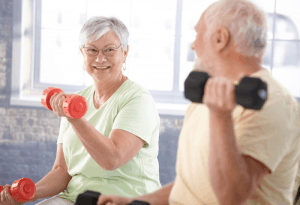 Two elderly actively lifting weights in their home