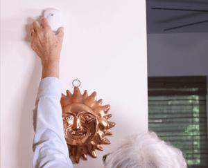 An elderly woman installing a Family Guardian sensor