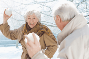Elderly couple snowball fighting
