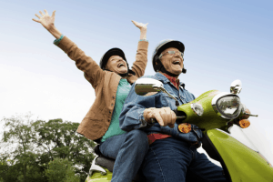 An elderly couple enjoying the travel on a moped