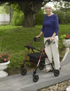 An elderly women walking with a rollator