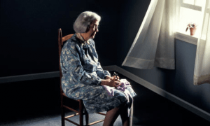 Lonely elderly mourning in a dark room