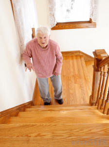An old women slowly moving up stairs