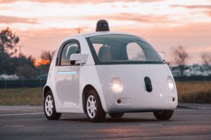 A compact white self-driving car standing in the sunset