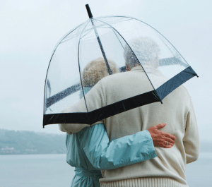 Senior couple standing in the rain with an umbrella
