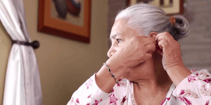 Senior putting in a hearing aid