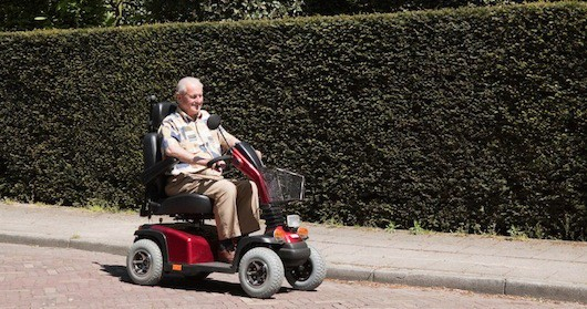 Senior man driving around on mobility scooter