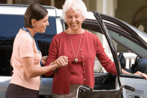 Traveling buddy helping senior get out of car