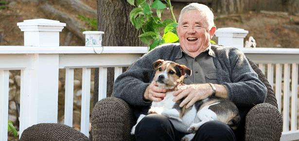 A senior gentleman with his dog sitting in the garden