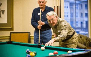 Two seniors enjoying a pool match in an independent living facility