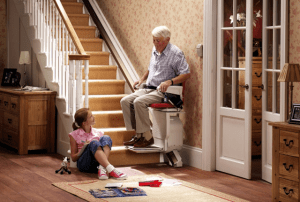 An elderly using a stairlift with his granddaughter